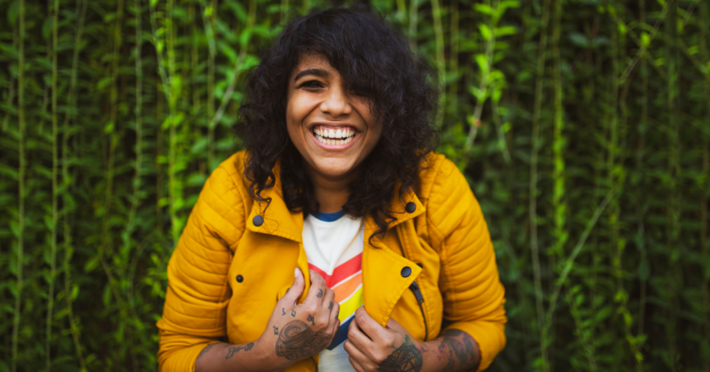 Woman wearing bright a yellow jacket, with a big smile on her face.